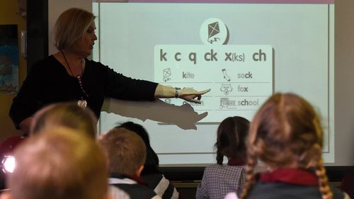 A teacher points at a board during a lesson at Stafford State School in Brisbane, Wednesday, Aug. 5, 2015.