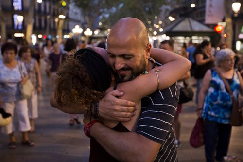 "A man hugs a woman, next to a banner reading ""I am muslim, I am not a terrorist. I share hugs of love and peace"" in Spain. (AP)"
