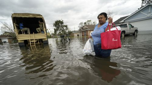 Jerilyn Collins returns to her destroyed home with the assistance of a Louisiana National Guard high-water vehicle to retrieve medicine for herself and her father, and a few possessions, after she evacuated from rising floodwater in the aftermath of Hurricane Ida in LaPlace, Louisiana.
