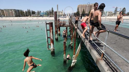 Teens jump of the jetty at Glenelg beach during a hot day in Adelaide.