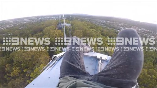 "The teenagers dangle their feet over a satellite dish before climbing back down, seemingly unhurt. Gold Coast Councillor Dawn Crichlow has slammed the stunt as ""too dangerous"". (9NEWS)"