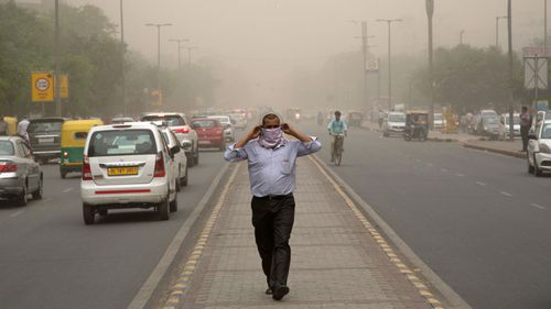 A man wraps a scarf around his nose as a dust storm envelops the city in New Delhi, India. (AP).