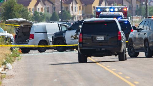 Police surround a white van believed to have been used in the shooting spree.