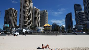 People lie on the beach at Surfers Paradise in Gold Coast, Australia.