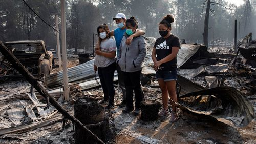 A family looks at the destruction of their home at Coleman Creek Estates mobile home park in Phoenix, Oregon.