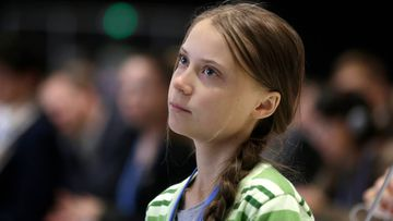 Swedish climate activist Greta Thunberg listens to speeches before addressing a plenary of U.N. climate conference at the COP25 summit in Madrid, Spain