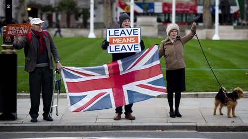 Brexit supporters stand outside the Houses of Parliament in London.