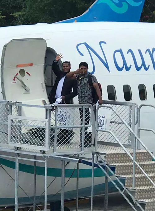 two Rohingya refugees waving as they board a United States bound plane in Nauru last month. (AAP)