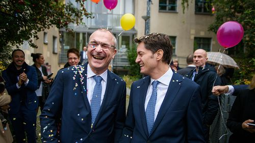 Volker Beck (l), Buendnis 90/Die Gruenen member of the German Bundestag, and his spouse Adrian Petkov are received by friends and family with confetti and balloons after getting married. (AAP)