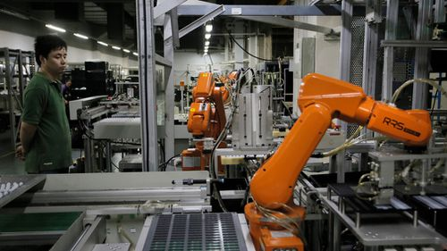 A Chinese man works amid orange robot arms at Rapoo Technology factory in southern Chinese industrial boomtown of Shenzhen. (AAP)