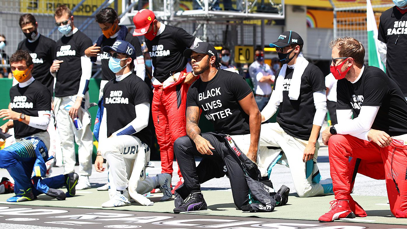 Lewis Hamilton of Great Britain and Mercedes GP and some of the F1 drivers take a knee on the grid in support of the Black Lives Matter movement