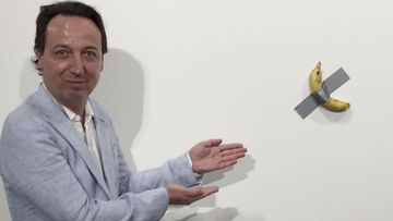 "Gallery owner Emmanuel Perrotin poses next to Italian artist Maurizio Cattlelan's ""Comedian"" at the Art Basel exhibition in Miami Beach, Florida."