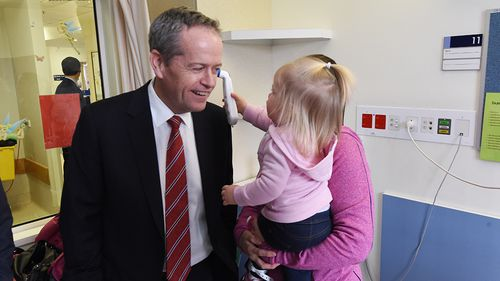 Bill Shorten gets his temperature checked by 20-month-old Katie Plowman at Casey Hospital. (AAP)