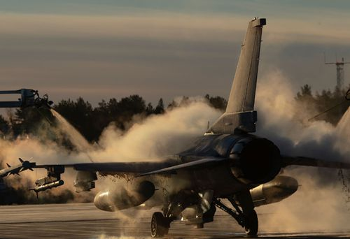 A US Air Force F-16 Fighting Falcon is de-iced ahead of the NATO wargames in northern Europe.