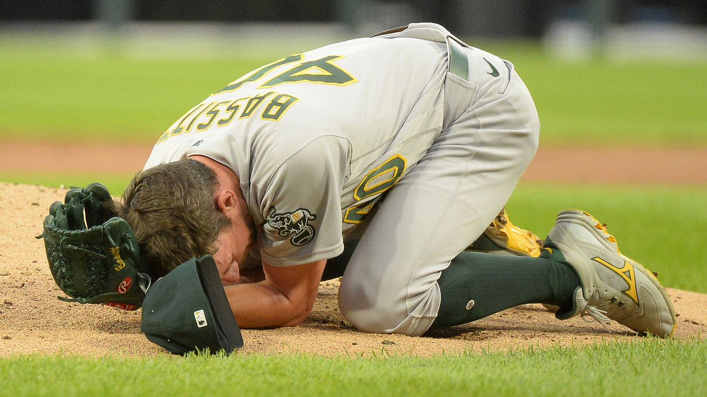 Chris Bassitt of the Oakland Athletics lies on the ground after being hit in the face by a line drive in the second inning off the bat of Brian Goodwin of the Chicago White Sox.