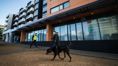 Staff from DHHS (Department of Health and Human Services Victoria) are seen walking the dogs of residents from the Ariele Apartments in Maribyrnong in Melbourne.
