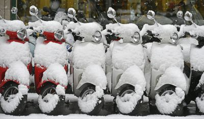 Switzerland: Vespas are covered in snow on a street in Zurich