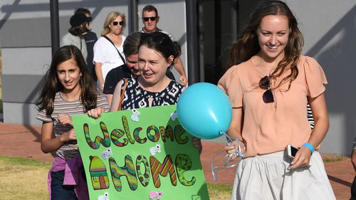 A group of girls welcome home Mallacoota bushfire evacuees at the Somerville Recreation Centre in Somerville south-east of Melbourne, Saturday, January 4, 2019. The group arrived at the port of Hastings on MV Sycamore this morning.