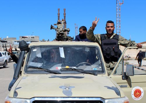 Militants, reportedly from the Misrata militia, flash the victory sign as they gather before heading to the frontline to join forces defending the capital, in Tripoli, Libya