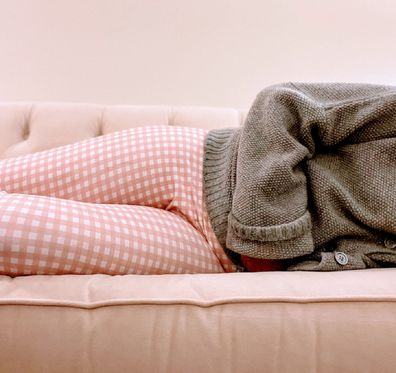 Woman lying down due to period pain.