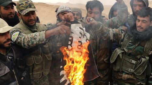 Syrian Army soldiers burning an ISIL flag. (AAP)