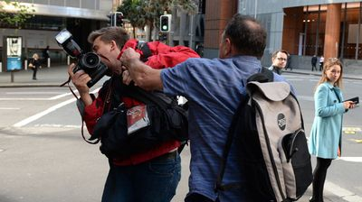 Former Australian Workers Union official Bruce Wilson attacks a photographer outside the Royal Commission into Trade Union corruption in Sydney. (AAP)