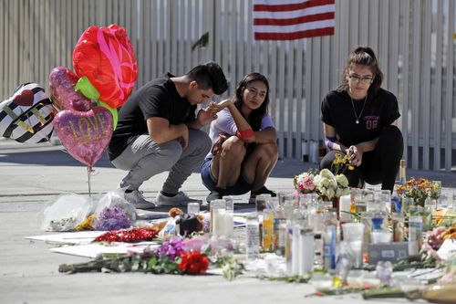 Roberto Lopez, from left, Briana Calderon and Cynthia Olvera, of Las Vegas, pause at a memorial site. (AAP)