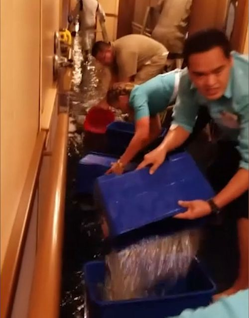Crew members are seen removing water after a water line break floods a Carnival cruise ship. (Supplied)