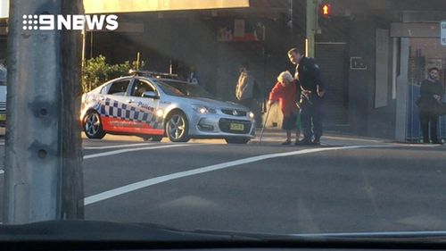 A witness told 9news.com.au not a single car honked as the officer helped the woman across the road. (9NEWS)