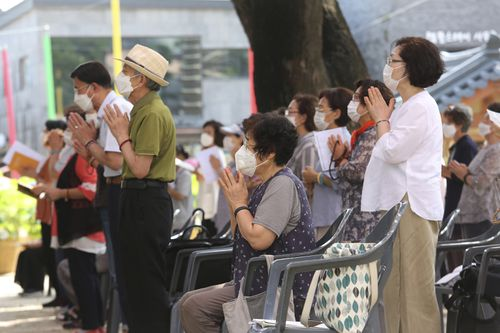 People wearing face masks to help protect against the spread of the coronavirus pray while maintaining social distancing during a service at the Chogyesa temple in Seoul, South Korea.
