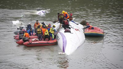 In this image, the commercial plane lies in the river as passengers cling to the craft which clipped a bridge shortly after take off. (Getty)