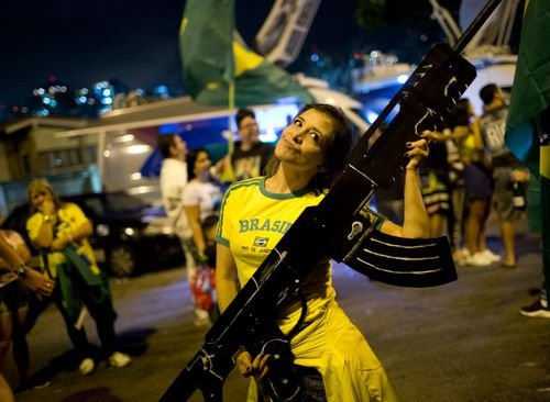This Bolsonaro supporter holds a huge imitation assault rifle after his victory. Loosening gun controls was a major policy of the far-right candidate.