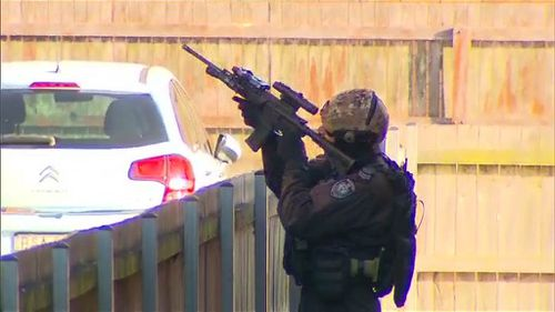 Heavily-armed police have raided an apartment in Sydney's southwest that turned out to be empty. (9NEWS)