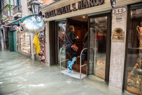 A tourist takes refuge from the sunken streets in a hotel.