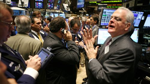 Traders, specialists and floor officials gather around the trading post where Lehman Brothers stock is traded on the floor of the New York Stock Exchange in 2008. (AAP)
