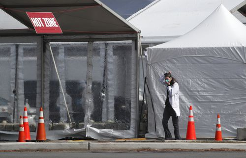 """A medical worker adjusts her face mask while approaching a """"Hot Zone"""" tent, Thursday, March 19, 2020, at one of several such tents at a state-managed cororonavirus drive-through testing site Picture: Kathy Willens"""