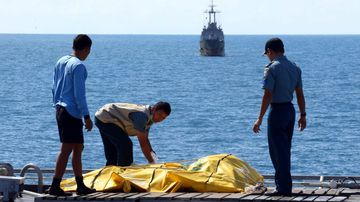 Indonesian rescuers inspect body bags of victims of crashed AirAsia flight QZ8501. (AAP)