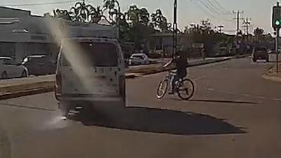 Cyclist rides into oncoming traffic without helmet