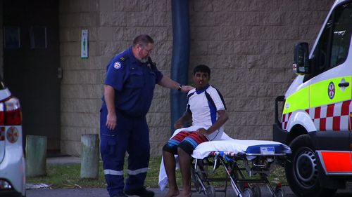 A NSW Ambulance worker comforts a man on a stretcher after two men drowned and one is still missing north of Coffs Harbour in NSW.
