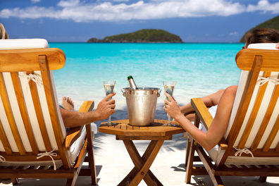 Couple drinking champagne in sun chairs on a beach   Honeymoon holiday couple