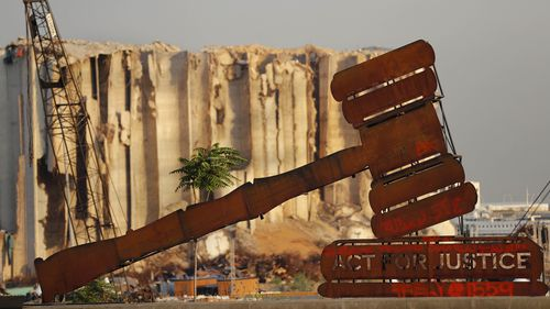 A justice symbol monument is seen in front of towering grain silos that were gutted in the massive August 2020 explosion at the port that claimed the lives of more than 200 people, in Beirut, Lebanon.