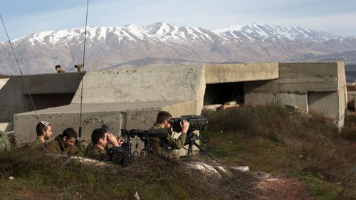Israeli soldiers taking positions next to the Israeli-Syrian border following the Israel attack in Syria. (AAP)