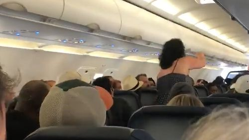 Two male passengers intervene in what appears to be an attempt to calm the woman – to no avail. Picture: Facebook/Chianti Washington