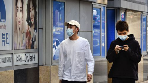 Zhang Bin, right, walks with a friend along a street, both wearing protective masks in the Koreatown section of Los Angeles.