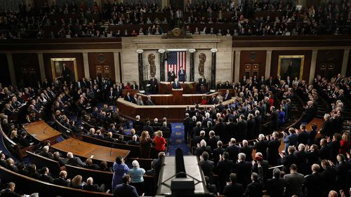 Democrats on the left stay seated while Republicans give a standing ovation to Donald Trump during his State of the Union. (AAP)