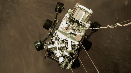The Perseverance rover lowered towards the surface of Mars.