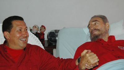 In this Aug. 13, 2006  photo released by Cuba's Communist daily newspaper Granma, Cuba's leader Fidel Castro, right, and Venezuela's President Hugo Chavez hold hands as Castro recuperates from surgery in Havana, Cuba. (AAP)