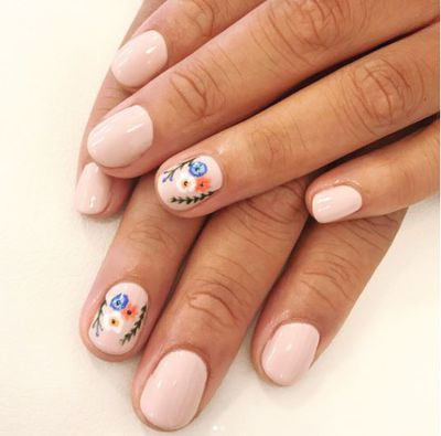 A nude-colored nail with a floral twist