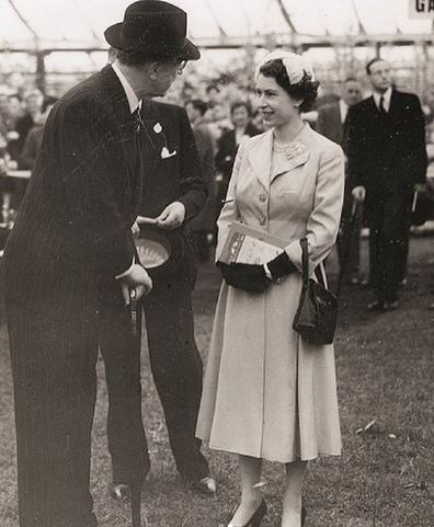 Queen Elizabeth speaks with officials during one of her first appearances at the Chelsea Flower Show.