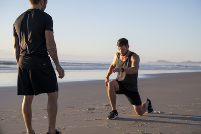 Chris Hemsworth working out with Luke Zocchi on a beach